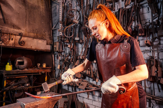 redhead ginger woman blacksmith portrait in workshop
