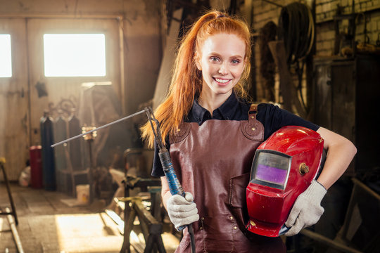 Strong and worthy pretty redhead ginher woman wearing protection helmet and leather apron with gloves holding welding machine instrument . small business concept