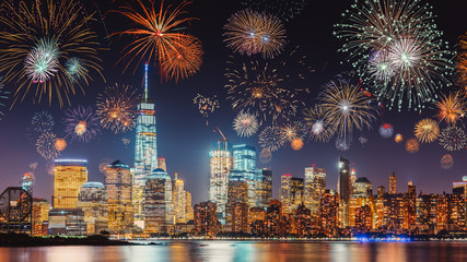 Foto auf Leinwand New York New Years Eve with colorful Fireworks over New York City skyline long exposure with dark blue-purple sky, orange city light glow and reflections in the river