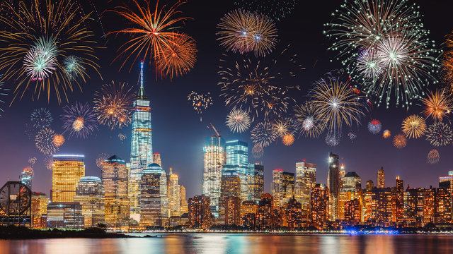 New Years Eve with colorful Fireworks over New York City skyline long exposure with dark blue-purple sky, orange city light glow and reflections in the river