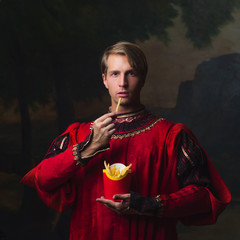 handsome man in a Royal red doublet eating French fries