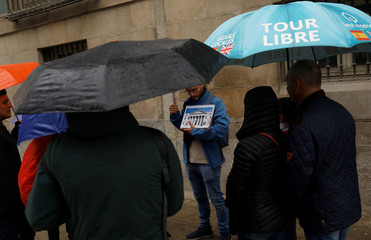 A tour guide shows to tourists a picture of Spain's parliament ahead of general election, in downtown Madrid
