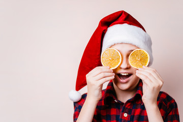christmas time. funny cute boy in santa hat closing eyes with dried orange slices. Holiday treats concept