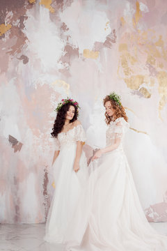 Two charming brides in beautiful spring wreaths on their heads. Beautiful young women in wedding dresses