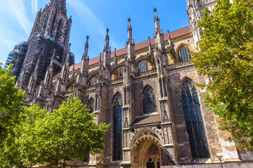 Wall Mural - Ulm Minster or Cathedral of Ulm city, Germany. It is a famous landmark of Ulm. Ornate facade of Gothic church in summer. Scenery of medieval European architecture on sunny day.