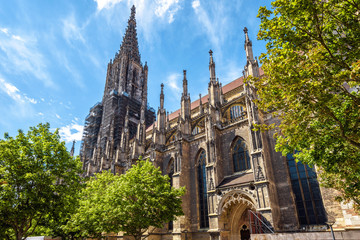 Fototapete - Ulm Minster or Cathedral of Ulm city, Germany. It is a famous landmark of Ulm. Panorama of ornate facade of Gothic church in summer. Scenery of medieval European architecture on sunny day.