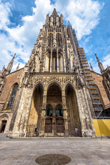 Fototapete - Ulm Minster or Cathedral of Ulm city, Germany. It is a top landmark of Ulm. Front view of ornate entrance of old Gothic church in summer. Facade of famous medieval temple on sunny day.