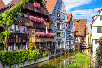 Fototapete - Vintage street with houses decorated by flowers in old town of Ulm, Germany. Nice view of historical Fisherman`s Quarter in summer. It is a landmark of Ulm. Ancient district of Ulm city with canals.