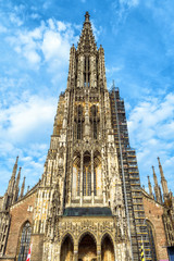 Fototapete - Ulm Minster or Cathedral of Ulm city, Germany. It is a top landmark of Ulm. Front view of ornate tower of old Gothic church in summer. Majestic facade of famous medieval temple.
