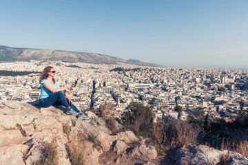 Fototapete - Young pretty woman looks at Athens city, Greece. Beautiful adult girl tourist relaxes overlooking Athens in summer. Attractive person is on background of urban landscape. Travel and vacation concept.