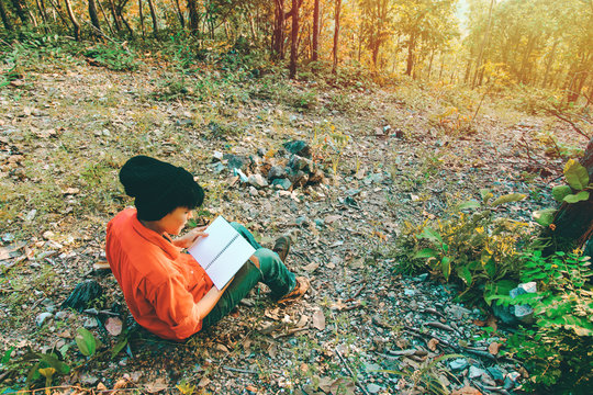 Asian students sitting on the floor of a mountain, are reading a book outside the forest and light sunset. Alone camping hiking lifestyle in environment nature autumn forest.