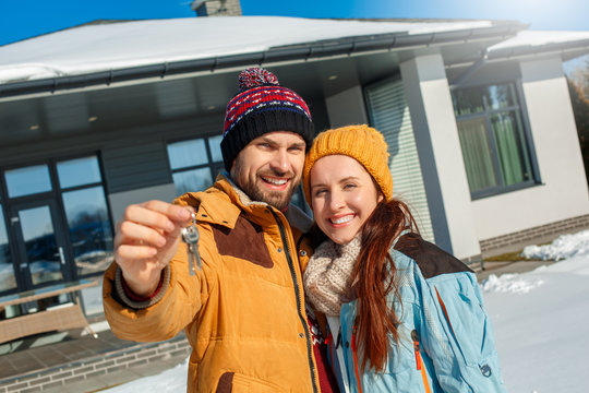 Winter vacation. Young couple standing together outdoors with keys from new house close-up smiling cheerful blurred