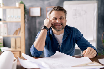 Smiling mature engineer sitting by table while working over new sketches