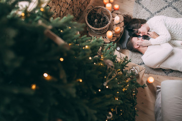 Photo shoot in the studio of a young married couple. Photographing of pregnancy. A guy with a girl is celebrating Christmas. New Year's love story.