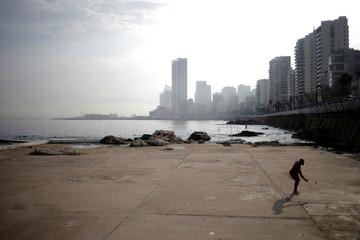 A man plays with a beach racket on a beach of Beirut