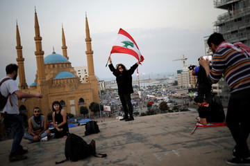 "A woman holds a Lebanese flag as a man takes a picture of her on the roof of of an abandoned cinema known as ""The Egg"", with Mohammad Al-Amin mosque in the background, in Beirut"