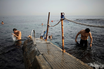 Men take a bath on a beach of Beirut