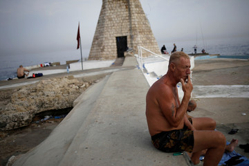 A man smokes a cigarette at a beach in Beirut