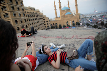 """A group of women stay on the roof of an abandoned cinema known as """"The Egg"""", with Mohammad Al-Amin mosque in the background, in Beirut"""