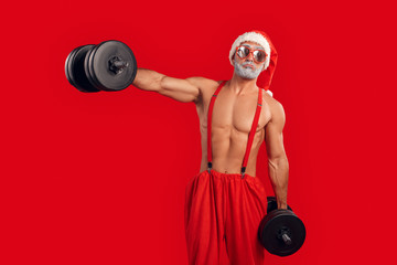 Adult nude Santa Claus making sportive trainings with dumbbell