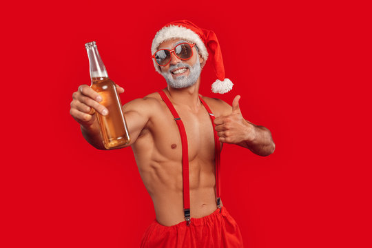 Christmas Freestyle. Young bearded Santa Claus bare muscular upper body in hat standing isolated on red with beer thumb up smiling happy