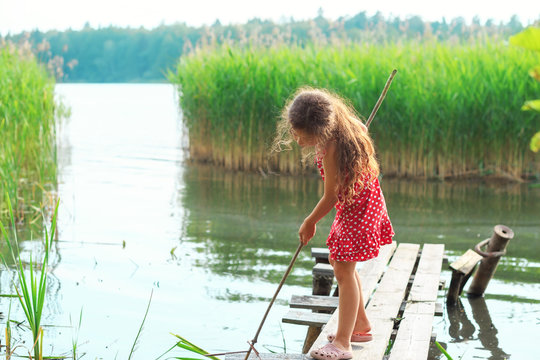 Cute Little girl is playing and looking at the lake at summer day.Place for text