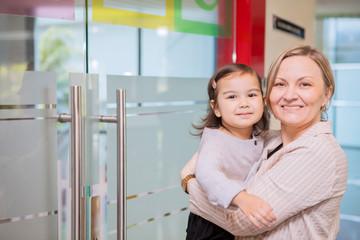 Happy mother accompanies her daughter to school