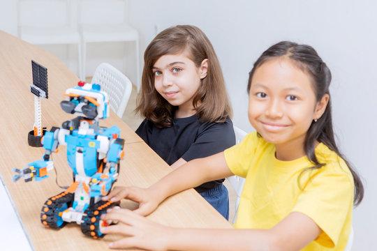 Two cute girls constructing a Lego robot in class
