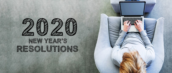 2020 New Years Resolutions with man using a laptop in a modern gray chair