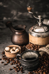 Wall Mural - Coffee cup with coffee grinder and coffee beans on dark textured background.