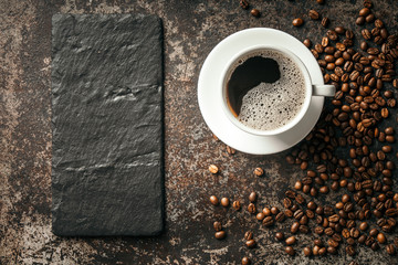 Wall Mural - Coffee cup and coffee beans on dark stone background.