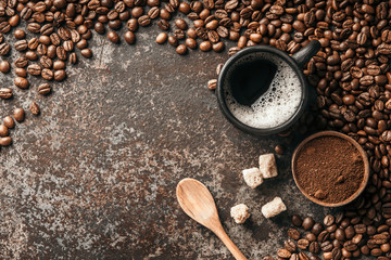 Fototapete - Coffee cup and coffee beans on dark stone background. Top view with copy space. Background with free text space.