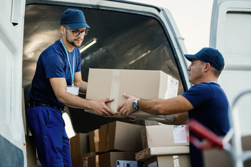 Young couriers cooperating while unloading packages from delivery van.