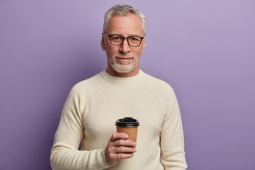 Grey haired senior man wears transparent glasses and white sweater, stands and cools hot beverage, enjoys pleasant conversation, poses against purple background. People, age, lifestyle concept