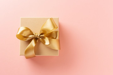 Gift box with golden ribbon on pink background
