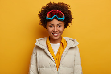Sports holidays, travel lifestyle and winter adventure concept. Glad African woman with toothy smile, snowboards in mountains, wears ski goggles and white down padded coat, isolated on yellow wall
