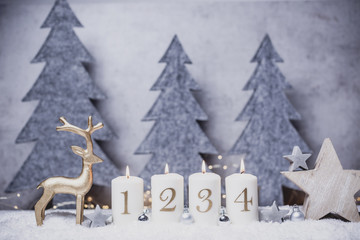 advents candles with flame and snow background in front of concrete and gray felt fir-tree