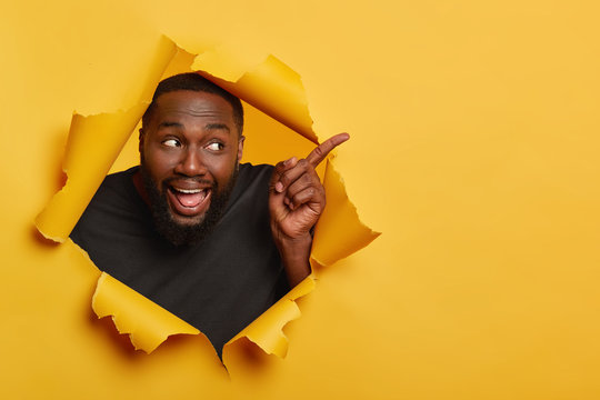 Photo of happy cheerful black male model points index finger aside, keeps mouth opened, shows tongue, attracts your attention to blank space, invites you going there, recommends product. Advertisement