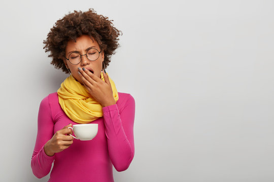 Tired curly woman yawn, has sleepy expression, drinks coffee early in morning, holds white muf of hot beverage, fatigue after work, wears bright stylish clothes, isolated on white wall, empty space