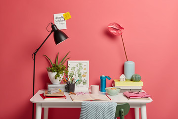 Indoor shot with no people, white desk of student with lamp, opened notebook, books, thermos of coffee, rosy calla lilies in vase pink wall sticky notes insctibed motivation phrases. Cozy workplace