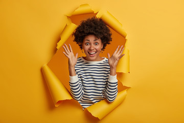 Image of overjoyed pleased young African American lady keeps both hands raised, glad to hear something awesome, grins at camera happily, wears striped jumper, poses through yellow torn hole.