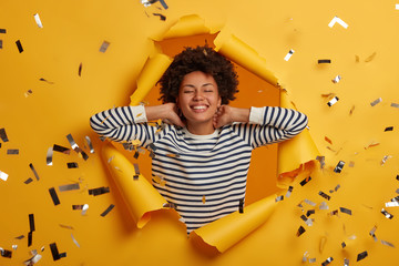 Relieved dark skinned woman has eyes closed, smiles broadly, keeps hands behind head, wears striped casual jumper, imagines something pleasant, enjoys weekends, poses in paper hole of bright wall
