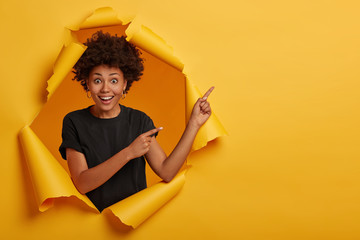 Nice attractive female model with crisp hair points aside, demonstrates advertisement, feels cheery and curious, wears black t shirt, stands in hole of paper wall shows yellow bright vivid copy space.