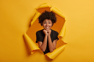 Photo of charming cute young African American girl smiles pleasantly at camera, keeps both hands under chin, shows white teeth, dressed in black clothing, has shining eyes, poses in paper hole