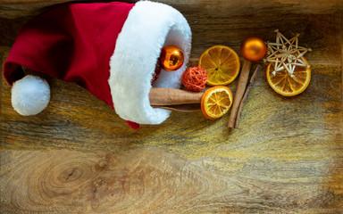 weihnachtlicher Hintergrund aus Holz mit Weihnachtsmütze und Dekorationen