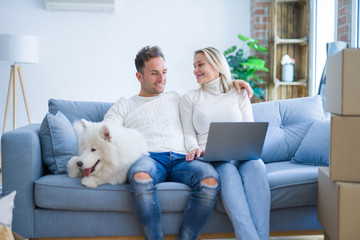Young beautiful couple with dog sitting on the sofa using laptop at new home around cardboard boxes