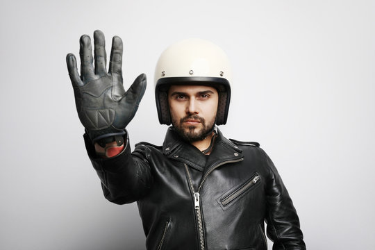 Close-up portrait of biker guy with white helmet making stop signs with his hand. Isolated.