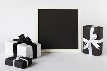 Presentation photo picture frame with black empty blank paper and three gift present boxes on white background.