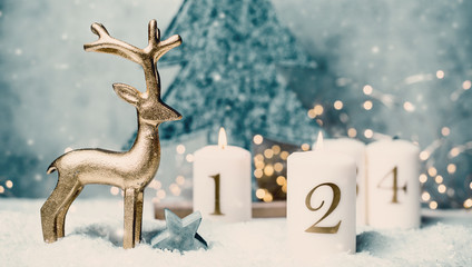 Advent candles 1, 2,3,4 in front of concrete background and reindeer in the snow with colorful lights and gray trees