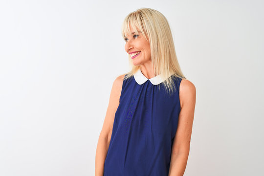 Middle age woman wearing elegant blue dress standing over isolated white background looking away to side with smile on face, natural expression. Laughing confident.